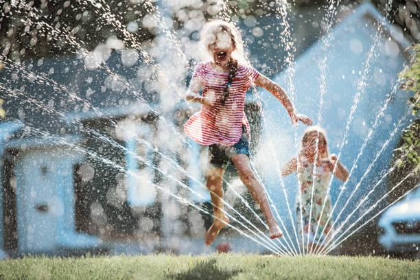 Mutlu çocuklar Bahçe Yağmurlama ile oynuyor stok fotoğrafı
