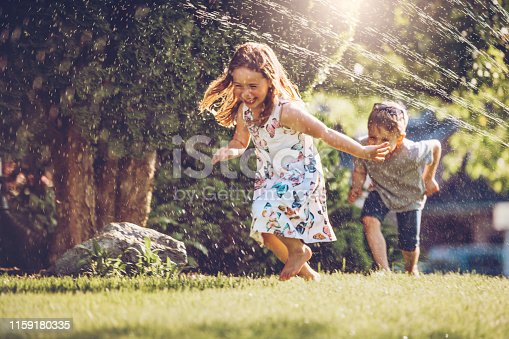 istock Happy kids playing with garden sprinkler 1159180335