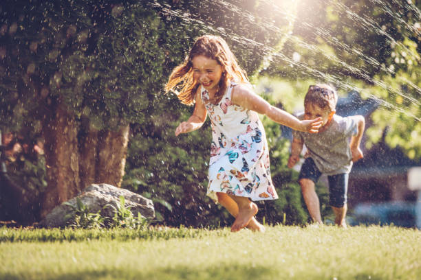 Happy kids playing with garden sprinkler Kids playing with sprinkler lawn stock pictures, royalty-free photos & images
