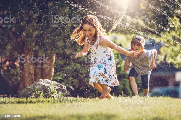 Photo of Happy kids playing with garden sprinkler