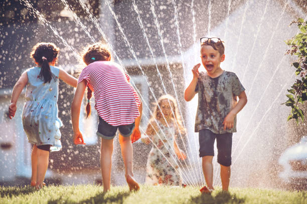 Happy kids playing with garden sprinkler stock photo