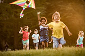 Group of happy kids having fun while running with a kite during spring day at the park.