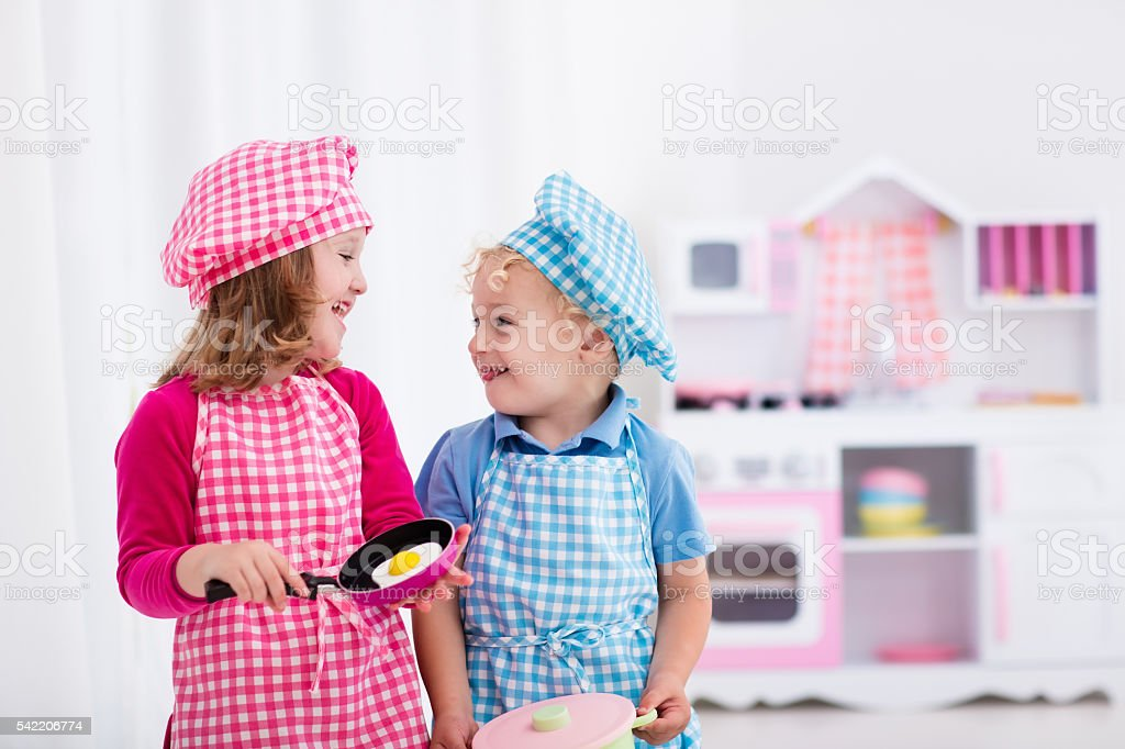 Happy kids playing with toy kitchen stock photo