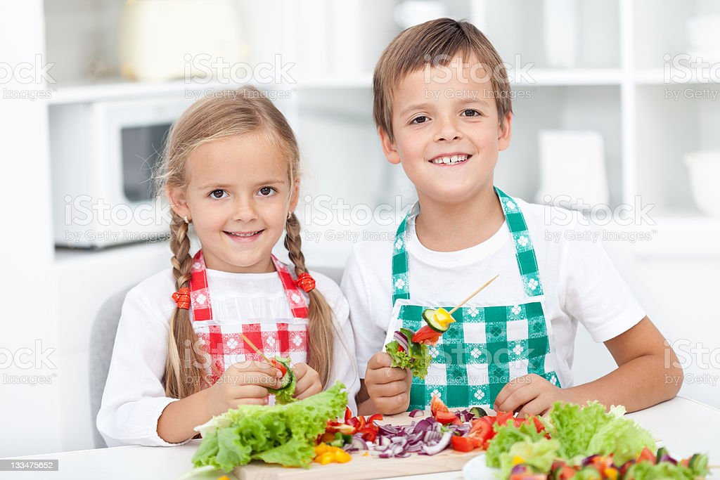 Happy kids preparing a meal in the kitchen royalty-free stock photo