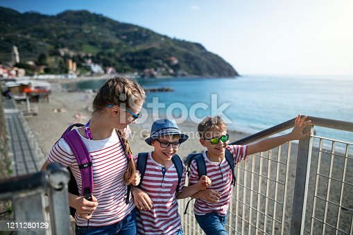 Thee kids returning from beach in April. Kids are walking on stairs, talking and laughing. Cinque Terre, Italy Sunny Spring day. Nikon D850