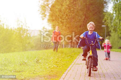 istock happy kids riding scooter and bike in the park 510225554