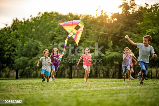 Group of happy children running with a flying dragon in public park