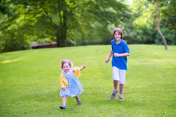 glückliche kinder laufen in einem park - hofkleider stock-fotos und bilder