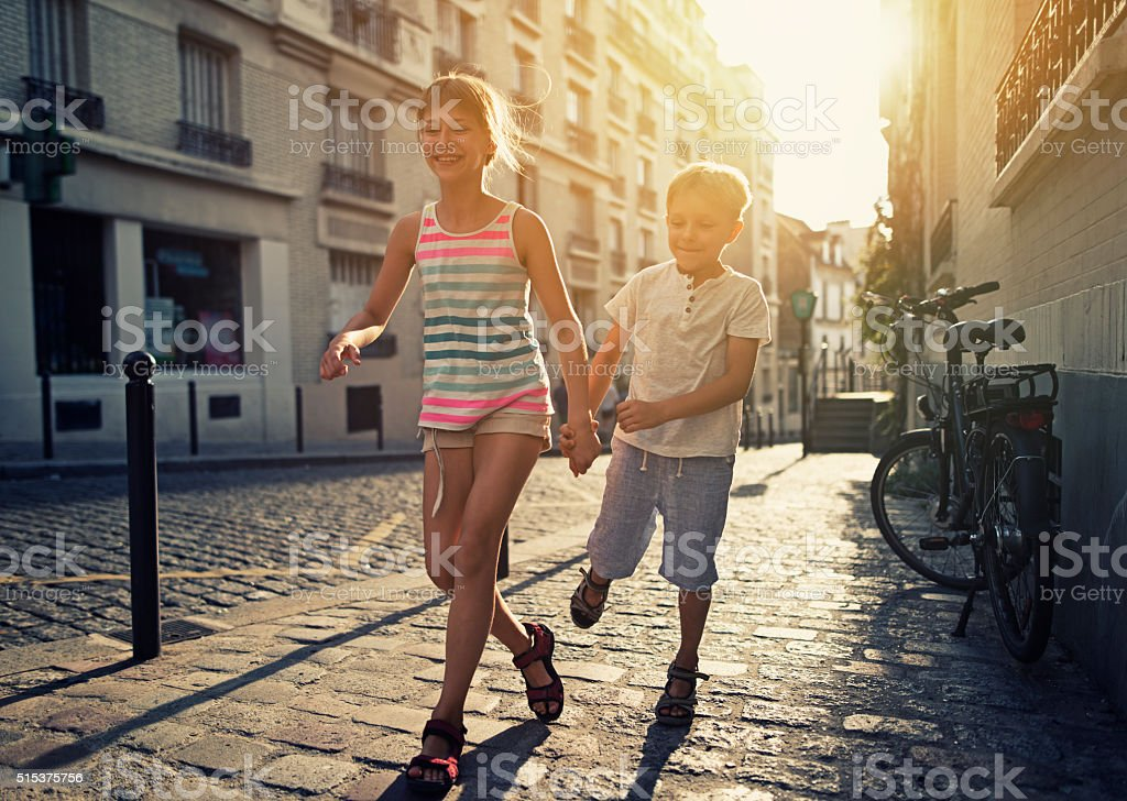 Sister with younger brother running in beautiful street of Paris....