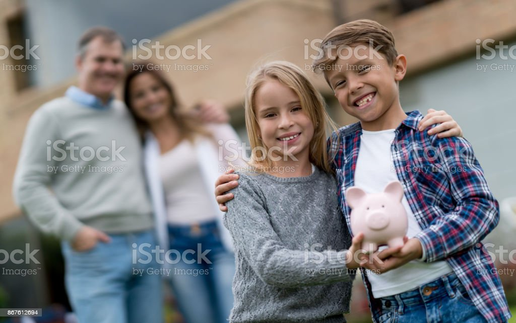 Happy kids saving money with their parents in a piggybank stock photo