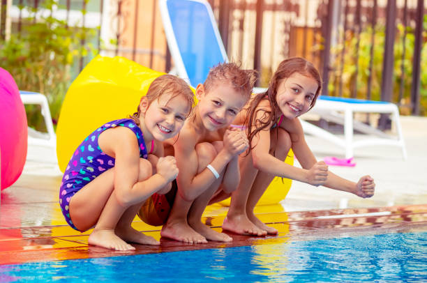 Glückliche Kinder sitzen in der Nähe der Pools – Foto