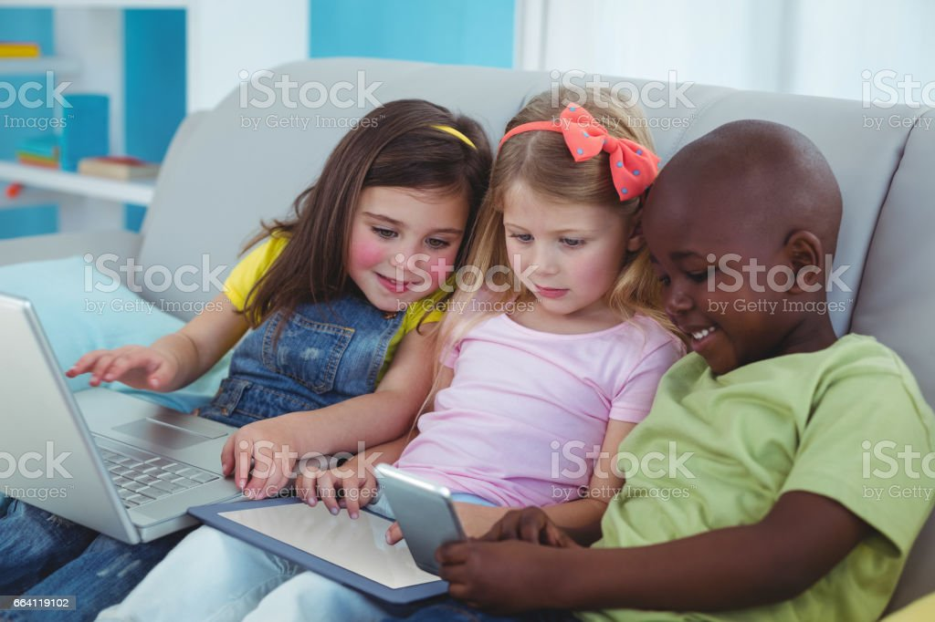 Happy kids sitting together with a tablet and laptop and phone foto stock royalty-free