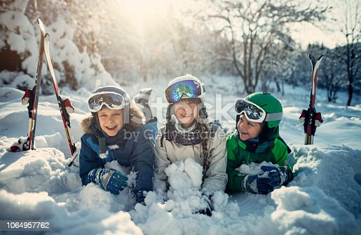 Kids playing in snow in winter forest. Girl aged 12 and two boys aged 7 are having fun on a sunny winter day. Nikon D850