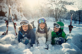 Kids playing in snow in winter forest. Girl aged 12 and two boys aged 7 are having fun on a sunny winter day.\nNikon D850
