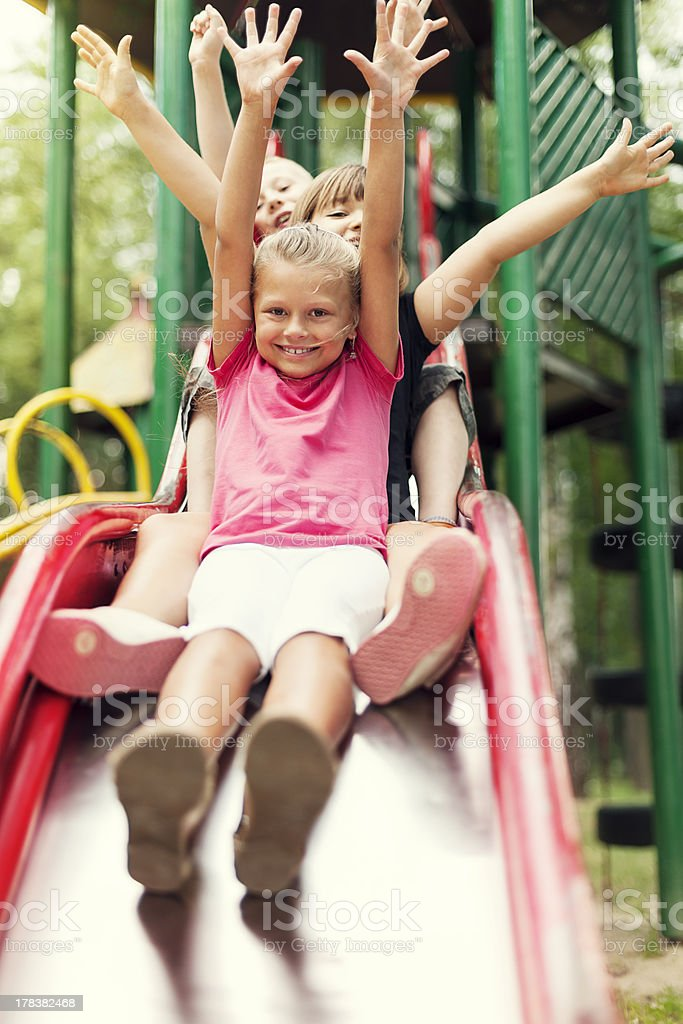 Happy kids slide on playground stock photo