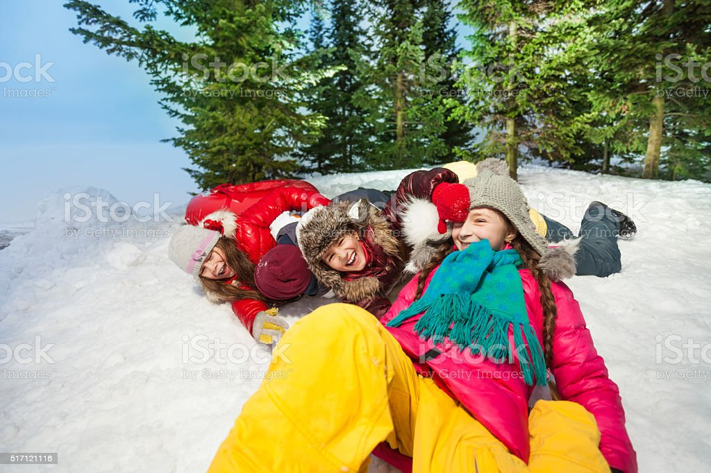 Happy kids sliding head over heels from the hill stock photo