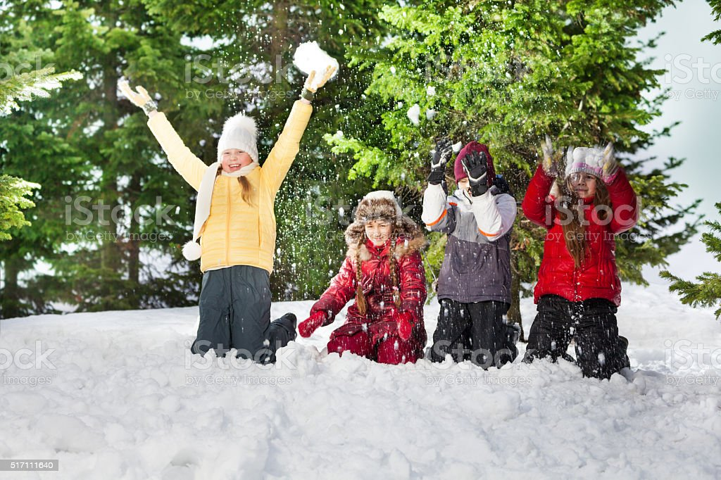 Happy kids standing on knees at sunny winter day stock photo
