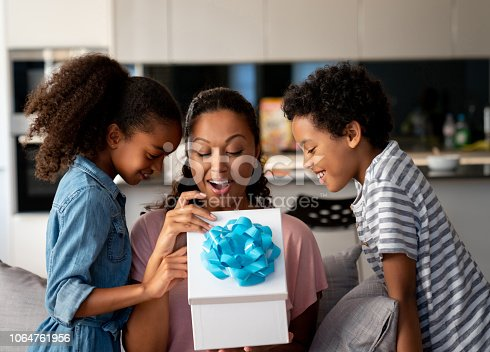Happy African American kids surprising their mother with a gift at home and smiling - Mother's Day concepts
