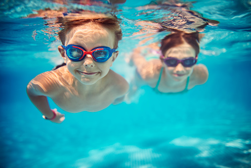 Smiling kids enjoying underwater swim in the pool towards the camera. Sunny summer day. Brother aged 5 is in the front, the sister is aged 9 and is swimming in the background. Slightly soft.