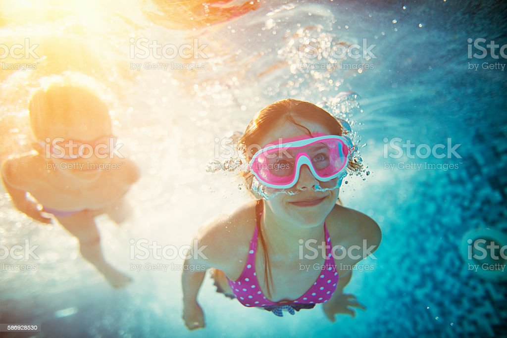Felice nuotare sott'acqua in piscina per bambini - foto stock