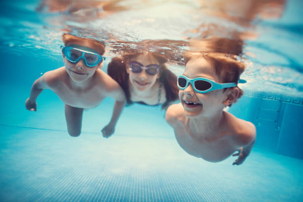 Happy kids swimming underwater in pool stock photo