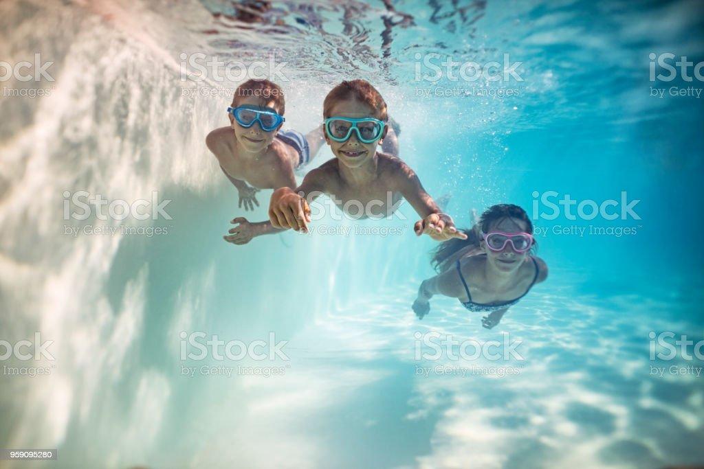 Happy kids swimming underwater stock photo
