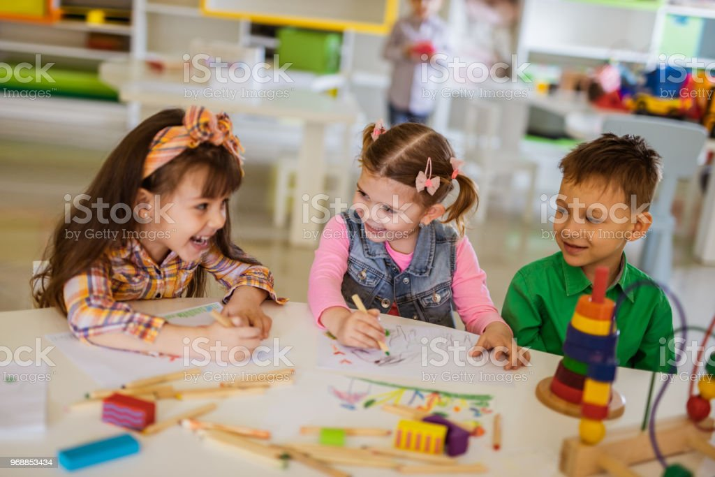 Group of happy little friends communicating while coloring in...