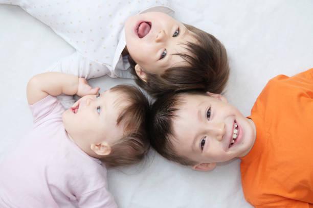幸せな子供 3 笑う子供異なる大きな家族に住んでいる兄弟の子供の頃に横になっている、少年の肖像画、小さな女の子と赤ちゃんの女の子、幸せを年齢します。 - 兄弟 ストックフォトと画像
