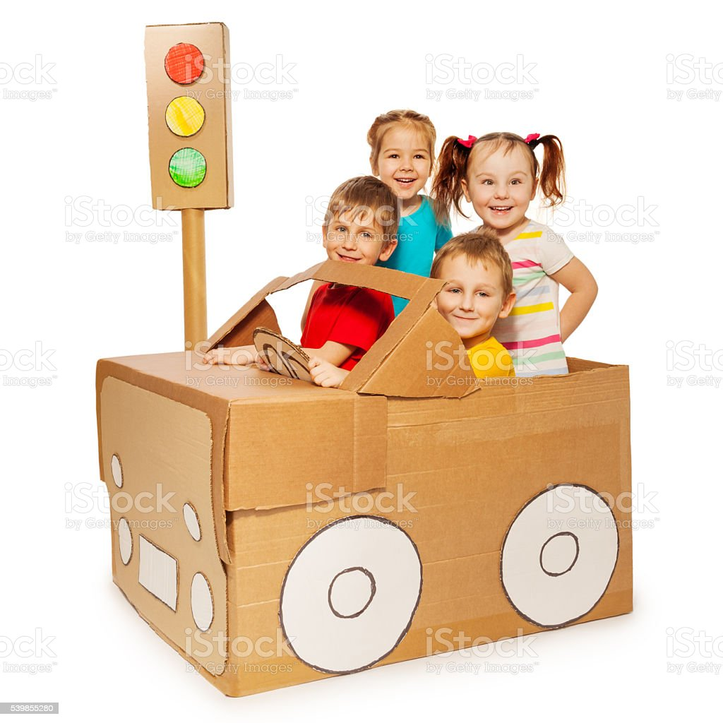 Happy kids travelling by cardboard car stock photo
