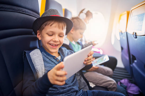 Happy kids travelling in plane stock photo