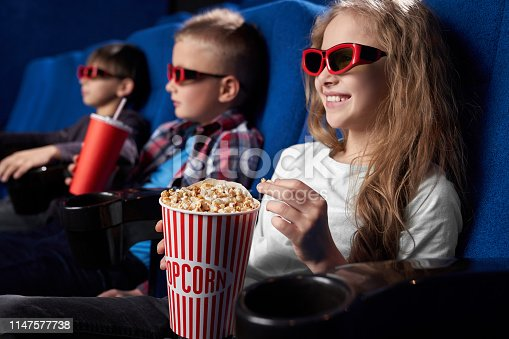 istock Happy kids watching movie in 3d glasses in cinema. 1147577738