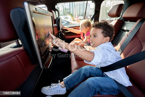 Portrait of two happy kids watching television in a car while wearing their seat belt fastened.  **DESIGN ON SCREEN WAS MADE FROM SCRATCH BY US**