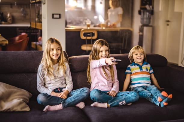 Happy kids auf Sofa im Wohnzimmer vor dem Fernseher. – Foto
