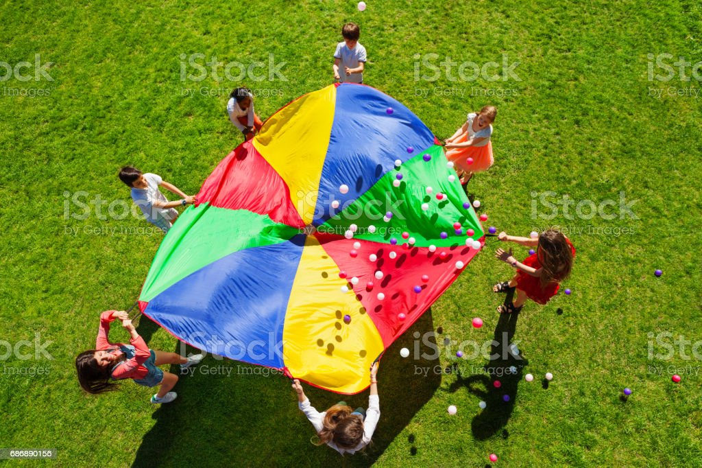 Happy kids waving rainbow parachute full of balls stock photo
