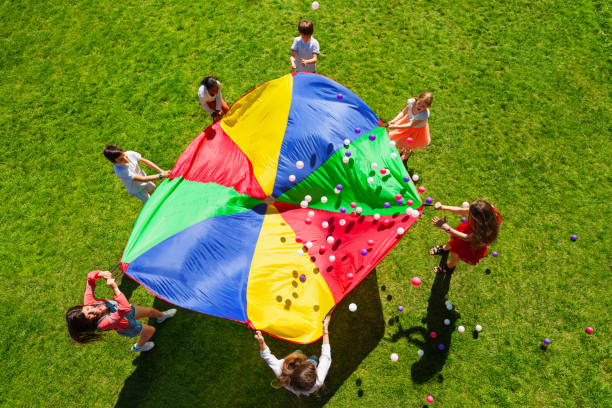Happy kids waving rainbow parachute full of balls stock photo