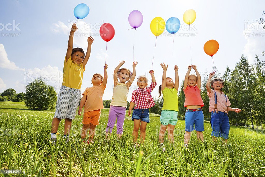 Happy kids with balloons and arms up in the sky stock photo