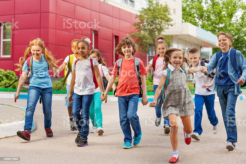 Happy kids with rucksacks walking holding hands stock photo