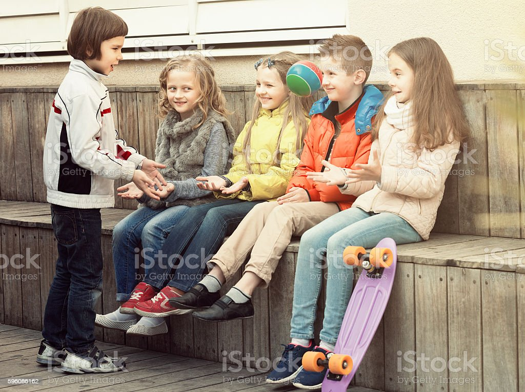 Happy kids with small ball playing in street stock photo