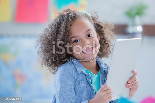 655532196 istock photo Happy kindergarten student smiles while using digital tablet technology 1081207764