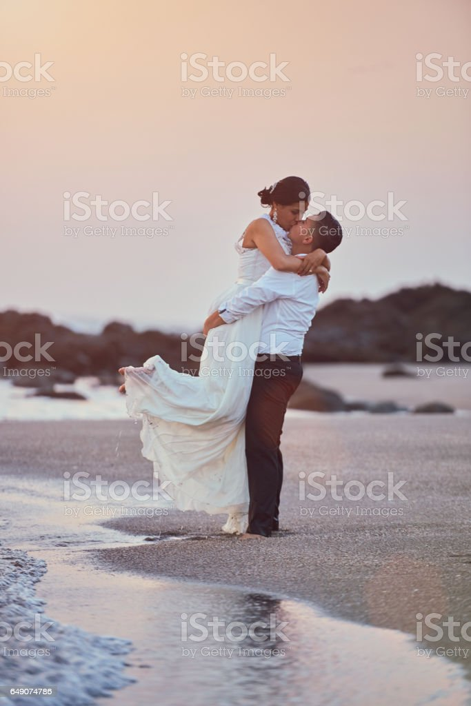 Happy kissing groom and bride stock photo