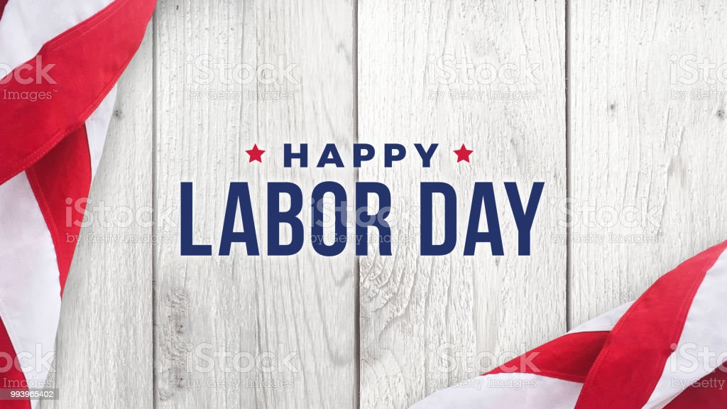 Happy Labor Day Text Over White Wood and American Flags stock photo