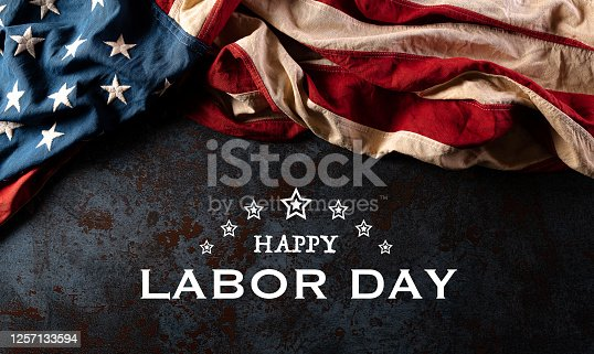 istock Happy labor day text with America flag over black stone texture background. 1257133594