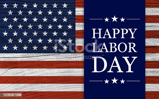 Labor Day background, with white texts on blue stripe over USA flag wooden background.