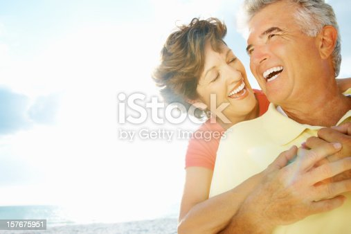 istock Happy lady embracing mature man from behind on a beach 157675951