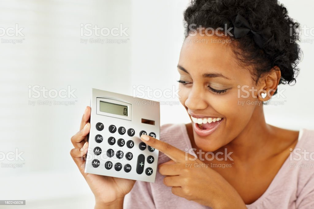 A happy lady holding a calculator in her right hand royalty-free stock photo