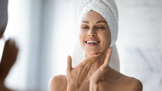 Happy lady look in bathroom mirror touching healthy face skin Happy confident young lady with towel on head look in bathroom mirror touching moisturized soft healthy sensitive skin doing morning hydration spa beauty routine, facial skincare treatment concept well structure stock pictures, royalty-free photos & images
