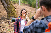 Happy lady posing and smiling on road in forest. Unrecognizable man taking photo of his girlfriend. Tourists hiking together in woods and having fun. Tourism, adventure and summer vacation concept