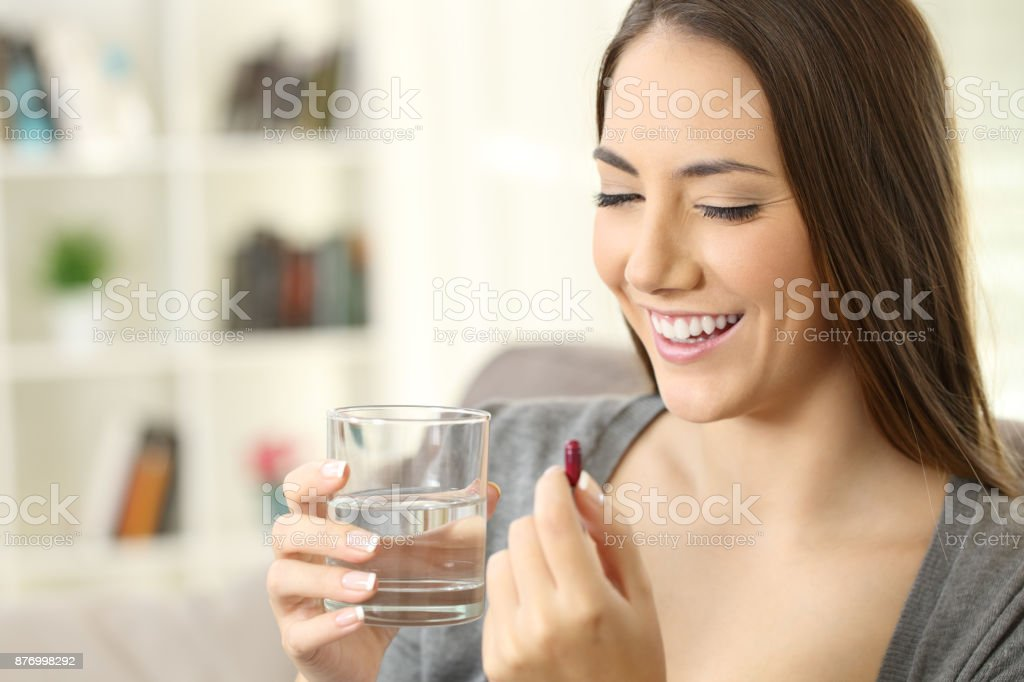 Happy lady ready to take a pill at home stock photo