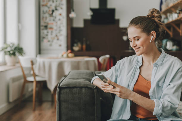 Happy lady sitting on couch with smartphone Technology in our life. Waist up portrait of young happy woman on sofa watching video on mobile phone with wireless earbuds bluetooth stock pictures, royalty-free photos & images