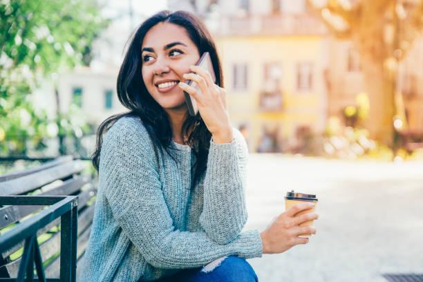 Glückliche Dame am Telefon spricht und hält Plastikbecher auf Bank – Foto